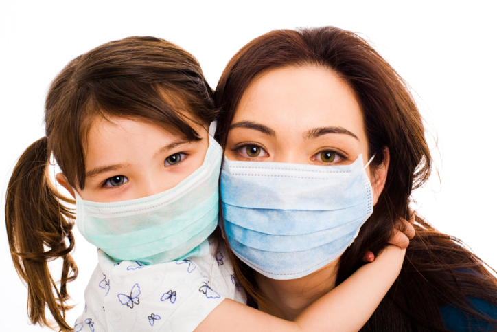 A portrait of a mother and little daughter wearing surgeon's masks